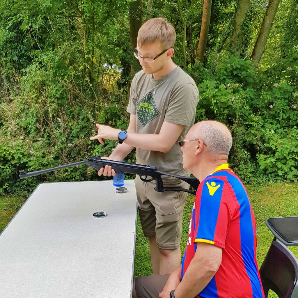 One of our volunteers teaching another volunteer how to use an air rifle.